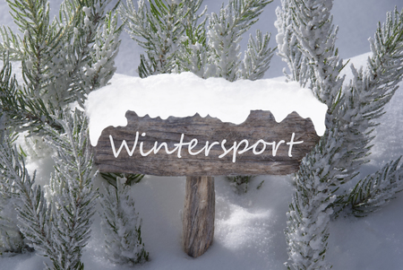 wintersport: Wooden Christmas Sign With Snow And Fir Tree Branch In The Snowy Forest. English Text Wintersport For Seasons Greetings Or Christmas Greetings. Christmas Atmosphere