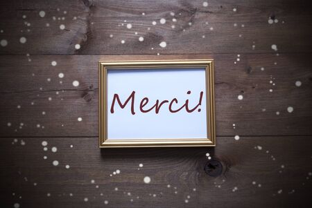 merci: One Golden Picture Frame On Wooden Background. French Text Merci Means Thank You. Rutic Vintage Or Retro Style. Snowflakes For Christmas Or Winter Atmosphere. Card For Seasons Greetings