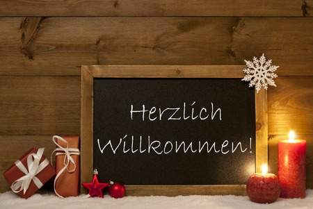 willkommen: Festive Christmas Card With Chalkboard, Red Gifts, Christmas Balls, Snowflake And Candles. Christmas Decoration With Vintage Wooden Background. German Text Herzlich Willkommen Mean Welcome Stock Photo