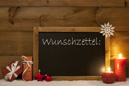 wish list: Festive Christmas Card With Chalkboard, Red Gifts Or Presents, Balls, Snowflake And Candles. Decoration With Rustic,Vintage Brown Wooden Background. German Text Wunschzettel Mean Wish List