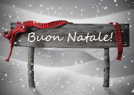 buon: Gray Wooden Christmas Sign On White Snow. Snowy Scenery, Snowflakes. Red Ribbon, Italian Text Buon Natale Means Merry Christmas. Christmas Card. Rustic Or Vintage Syle.Black And White Image