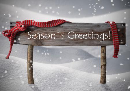 Brown Holz Weihnachten Zeichen auf weißem Schnee. Verschneite Landschaft, Schneeflocken. Red Ribbon, englischer Text Jahreszeit-Grüße. Weihnachtsschmuck oder Weihnachtskarte. Rustikal oder Vintage Syle Lizenzfreie Bilder