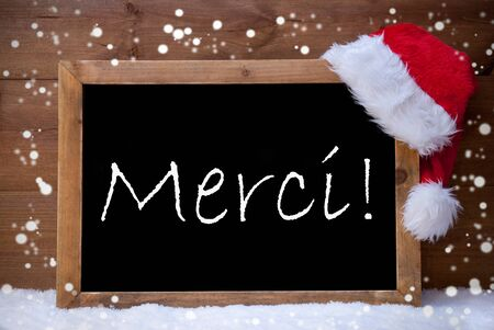 french text: Blackboard With Red Santa Hat On White Snow. French Text Merci Mean Thank You. Snowy Atmosphere With Snowflakes. Christmas Decoration With Brown Vintage Wooden Background Stock Photo