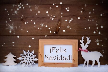 feliz navidad: Christmas Card With Brown Picture Frame On White Snow, Snowflakes And Sparkling Stars. Spanish Text Feliz Navidad Means Merry Christmas. White Decoration Like Tree And Reindeer And Wooden Background Stock Photo