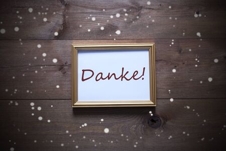 thankfulness: One Golden Picture Frame On Wooden Background. German Text Danke Means Thank You. Rutic Vintage Or Retro Style. Snowflakes For Christmas Or Winter Atmosphere. Card For Seasons Greetings Stock Photo