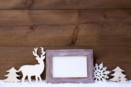 animal picture: Christmas Card With Shabby Chic Picture Frame On White Snow. Copy Space For Advertisement. Christmas Decoration Like Snowflake, Tree And Reindeer. Vintage, Wooden Background.