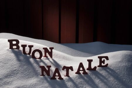 buon: Red Letters On White Snow As Christmas Card.  Italian Text Or Word Buon Natale Means Merry Christmas. Snowy Scenery And Atmosphere. Rustic Vintage Wooden Background Stock Photo