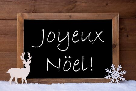 french text: Christmas Card, With Snowflake And Reindeer On White Snow. Brown, Rustic, Vintage Wooden Background.  Christmas Decoration With French Text Joyeux Noel Mean Merry Christmas