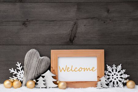 gold christmas decorations: Golden Christmas Decoration On Snow. Heart, Christmas Tree Balls, Snowflake, Christmas Tree. Picture Frame With English Text Welcome. Rustic, Vintage Gray Wooden Background. Black And Withe Image Stock Photo