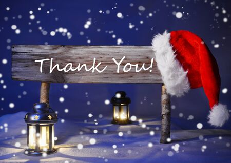 silent night: Wooden Christmas Sign And Santa Hat With White Snow In Snowy Scenery. English Text Thank You For Seasons Greetings. Blue Silent Night With Snowflakes. Lantern And Candlelight