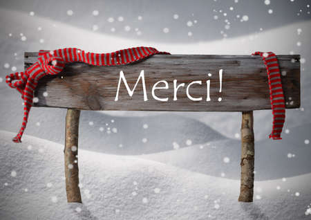 french text: Brown Wooden Christmas Sign On White Snow. Snowy Scenery, Snowflakes. Red Ribbon, French Text Merci Means Thank You. Christmas Decoration Or Christmas Card. Rustic Or Vintage Syle Stock Photo