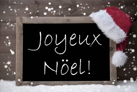 french text: Gray Blackboard With Red Santa Hat On White Snow, Snowflakes. French Text Joyeux Noel Mean Merry Christmas. Snowy Christmas Decoration With Brown Vintage Wooden Background. Black and White
