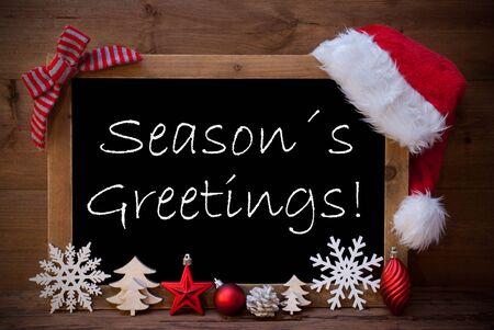 estaciones del año: Pizarra con Santa sombrero rojo y la decoración de Navidad como copo de nieve, árbol, la bola de Navidad, Cono de abeto, la estrella. Inglés texto saludos de las estaciones. Fondo de madera de Brown