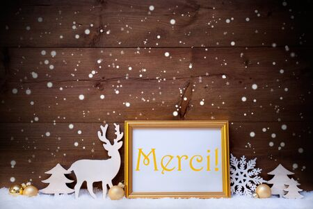 french text: Christmas Card With Picture Frame On White Snow. French Text Merci Means Thank You. White Decoration Like Snowflakes, Tree, Golden Balls And Reindeer. Vintage, Wooden Background Stock Photo
