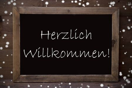 willkommen: Brown Blackboard With  German Text Herzlich Willkommen Means Welcome As Greeting Card. Wooden Background. Vintage Rustic Style. Snowflakes Symbolizing Christmas Or Winter Season. Stock Photo