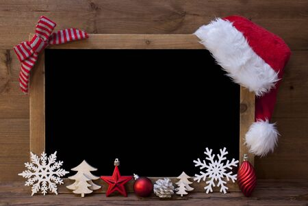 Brown Christmas Blackboard With Copy Space, Free Text As Greeting Card. Red Christmas Decoration, Loop, Santa Hat, Christmas Ball, Christmas Tree, Snowflake. Wooden Background. Vintage Rustic Style. Stock Photo