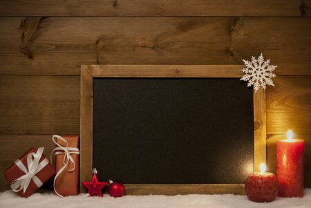 free christmas background: Festive Christmas Card With Chalkboard, Red Gifts Or Presents, Christmas Balls, Snowflake And Candles. Christmas Decoration With Rustic, Vintage Brown Wooden Background. Copy Space For Free Text Stock Photo