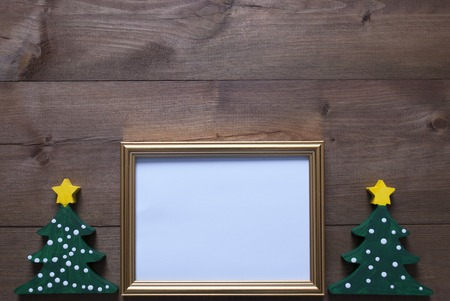 gold picture frame: One Golden Picture Frame With Two Green Christmas Tree. Copy Space For Advertisement. Christmas Card For Seasons Greetings. Christmas Decoration With Brown Wooden And Rustic Retro Background.