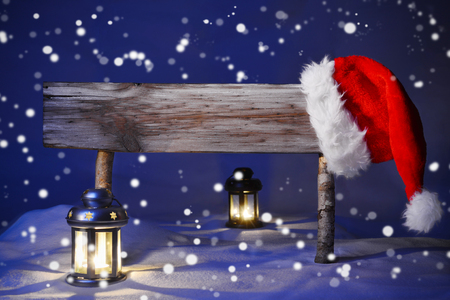 Wooden Christmas Sign And Santa Hat With White Snow In Snowy Scenery. Copy Space Free Text For Advertisement. Blue Silent Night With Snowflakes. Lantern And Candlelight