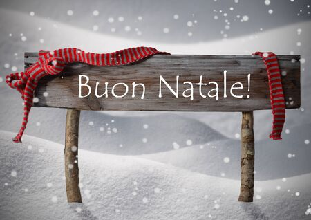 buon: Brown Wooden Christmas Sign On White Snow. Snowy Scenery, Snowflakes. Red Ribbon, Italian Text Buon Natale Means Merry Christmas. Christmas Card. Rustic Or Vintage Syle
