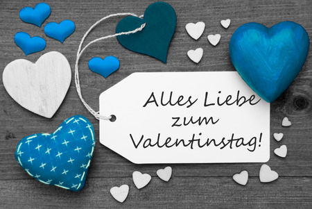 in liebe: Label With Blue Textile Hearts On Wooden Gray Background. German Text Alles Liebe Zum Valentinstag Means Happy Valentines Day. Retro Or Vintage Style. Black And White Image With Colored Hot Spot.