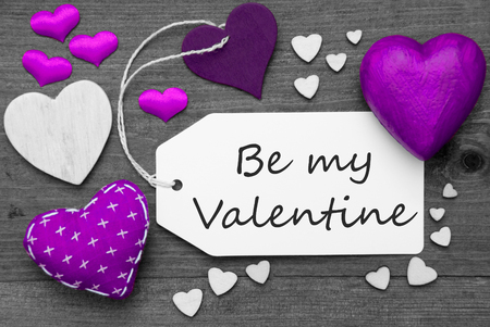 hot spot: Label With Purple Textile Hearts On Wooden Gray Background. English Text Be My Valentine. Retro Or Vintage Style. Black And White Image With Colored Hot Spot.