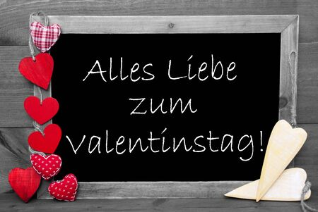 in liebe: Chalkboard With German Text Alles Liebe Zum Valentinstag Means Happy Valentines Day And Red Hearts. Wooden Background With Vintage, Rustic Or Retro Style. Black And White Image With Colored Hot Spots. Stock Photo