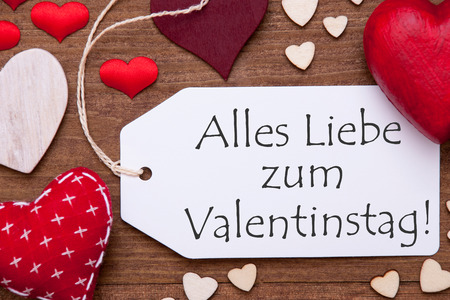 in liebe: Label With Red Textile Hearts On Wooden Gray Background. German Text Alles Liebe Zum Valentinstag Means Happy Valentines Day. Retro Or Vintage Style. Macro Or Close Up Of One Label