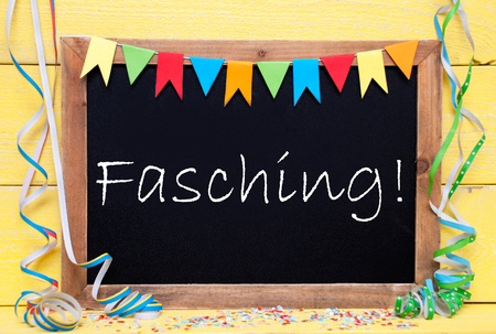 fasching: Chalkboard With German Text Fasching Means Carnival. Party Decoration Like Streamer, Confetti And Bunting Flags. Yellow Wooden Background With Vintage, Retro Or Rustic Syle