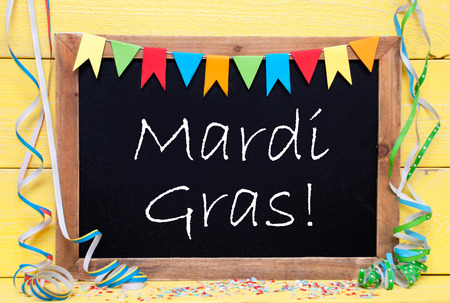 like english: Chalkboard With English Text Mardi Gras. Party Decoration Like Streamer, Confetti And Bunting Flags. Yellow Wooden Background With Vintage, Retro Or Rustic Syle