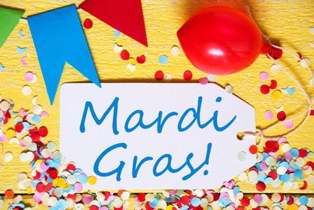 like english: One Label With English Text Mardi Gras. Party Decoration Like Balloon, Confetti And Bunting Flags. Yellow Wooden Background With Vintage, Retro Or Rustic Syle. Close Up View