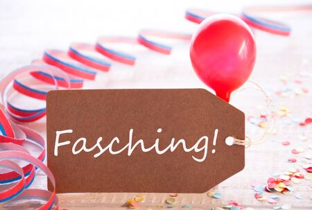 fasching: One Label With German Text Fasching Means Carnival. Party Decoration Like Streamer, Confetti And Balloon. Wooden Background With Vintage, Retro Or Rustic Syle Stock Photo