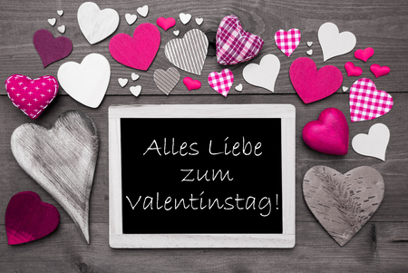 in liebe: Chalkboard With German Text Alles Liebe Zum Valentinstag Means Happy Valentines Day. Many Pink Textile Hearts. Wooden Background With Vintage, Rustic Or Retro Style. Black And White Image.