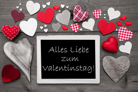 in liebe: Chalkboard With German Text Alles Liebe Zum Valentinstag Means Happy Valentines Day. Many Red Textile Hearts. Wooden Background With Vintage, Rustic Or Retro Style. Black And White Image.