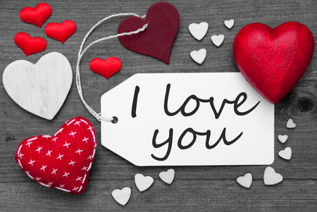 hot spot: Label With Red Textile Hearts On Wooden Gray Background. English Text I Love You. Retro Or Vintage Style. Black And White Image With Colored Hot Spot.