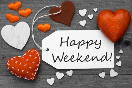 fin de semana: Etiqueta con textiles Corazones anaranjados en el fondo de madera gris. Inglés Texto feliz fin de semana. Retro o vintage estilo. Imagen blanco y negro con color Hot Spot. Foto de archivo