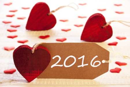 romantic label with many hearts text 2016 for happy new year greetings wooden background