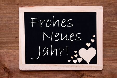 jahr: Blackboard With German Text Frohes Neues Jahr Means Happy New Year. Brown Wooden Hearts. Wooden Background With Vintage, Rustic Or Retro Style.