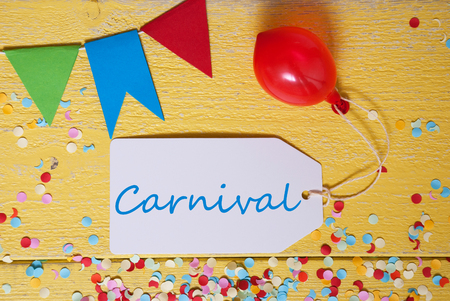 like english: One Label With English Text Carnival. Party Decoration Like Balloon, Confetti And Bunting Flags. Yellow Wooden Background With Vintage, Retro Or Rustic Syle