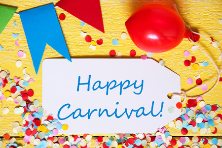 like english: One Label With English Text Happy Carnival. Party Decoration Like Balloon, Confetti And Bunting Flags. Yellow Wooden Background With Vintage, Retro Or Rustic Syle. Close Up View Stock Photo