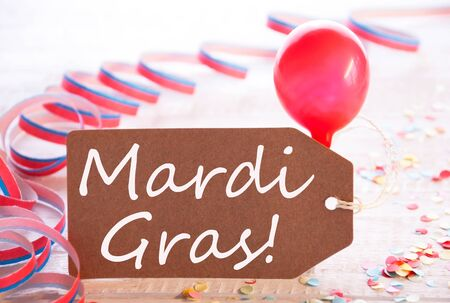 like english: One Label With English Text Mardi Gras. Party Decoration Like Streamer, Confetti And Balloon. Wooden Background With Vintage, Retro Or Rustic Syle Stock Photo