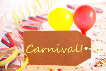 like english: One Label With Yellow English Text Carnival. Party Decoration Like Streamer, Confetti And Balloon. Wooden Background With Vintage, Retro Or Rustic Syle