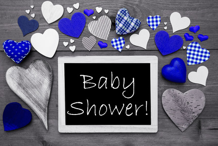 english text: Chalkboard With English Text Baby Shower. Many Blue Textile Hearts. Wooden Background With Vintage, Rustic Or Retro Style. Black And White Image With Colored Hot Spots. Stock Photo