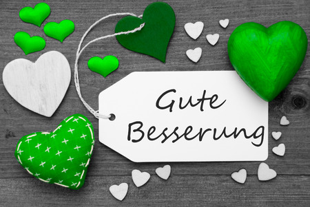 Label With Green Textile Hearts On Wooden Gray Background. German Text Gute Besserung Means Get Well Soon. Retro Or Vintage Style. Black And White Image With Colored Hot Spot.