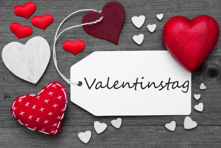 hot spot: Label With Red Textile Hearts On Wooden Gray Background. German Text Valentinstag Means Valentines Day. Retro Or Vintage Style. Black And White Image With Colored Hot Spot.