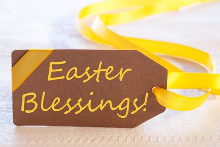 blessings: One Brown Label With Yellow Ribbon. English Text Easter Blessings. Card For Easter Greetings On Wooden Background