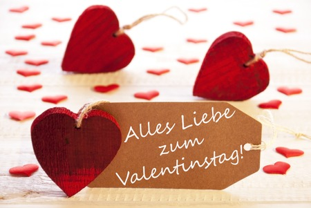 in liebe: Romantic Label With Many Hearts. German Text Alles Liebe Zum Valentinstag Means Happy Valentines Day. Wooden Background And Retro Or Vintage Style.