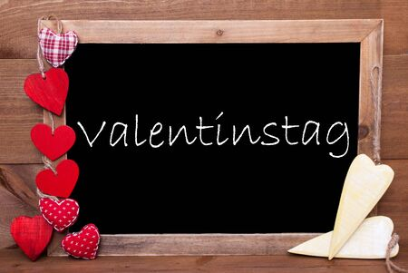 Chalkboard With German Text Valentinstag Means Valentines Day. Many Red  Textile And Wooden Yellow Hearts