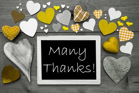 many thanks: Chalkboard With English Text Many Thanks. Many Yellow Textile Hearts. Wooden Background With Vintage, Rustic Or Retro Style. Black And White Image With Colored Hot Spots.