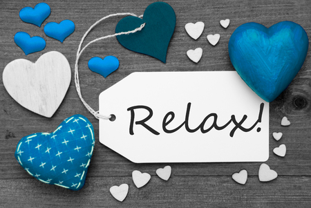 hot spot: Label With Blue Textile Hearts On Wooden Gray Background. English Text Relax. Retro Or Vintage Style. Black And White Image With Colored Hot Spot.